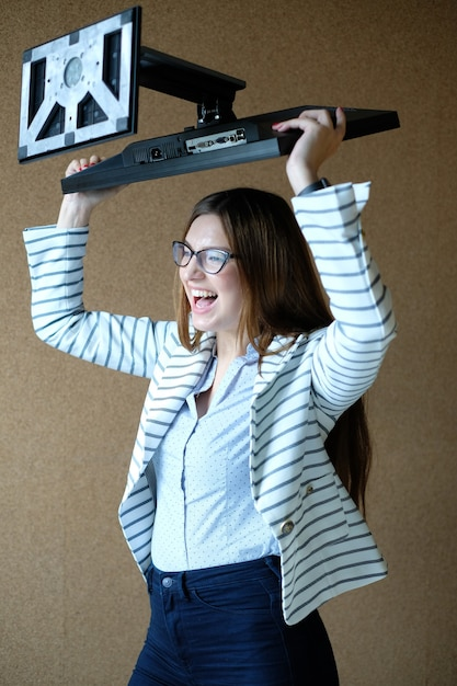 Молодая женщина, держащая экран монитора с яростью Бесплатные Фотографии