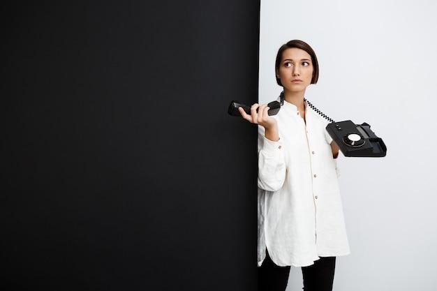 黒と白の表面に古い携帯電話を保持している若い女性 無料写真