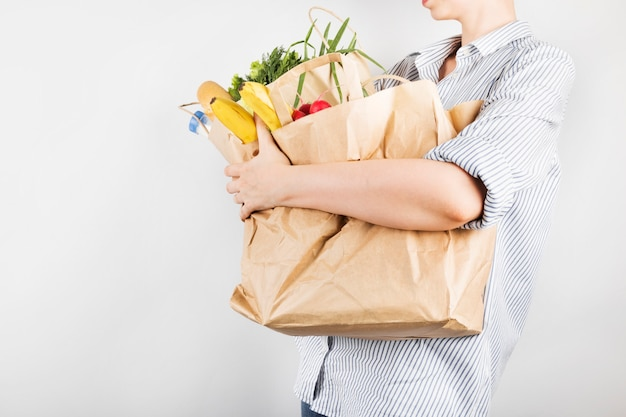 Young woman holding papers shopping bags on gray background Premium Photo