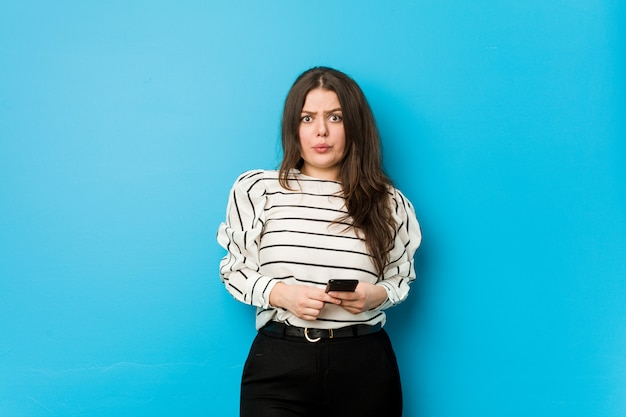 Young woman holding a phone shrugs shoulders and open eyes confused. Premium Photo