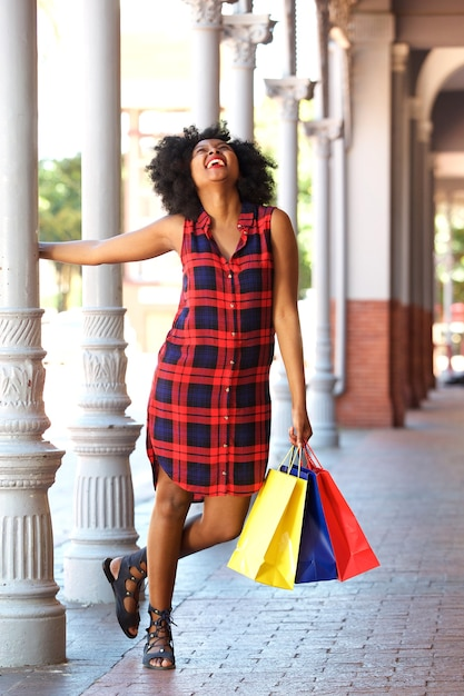Young woman holding on pillar with colorful bags Premium Photo