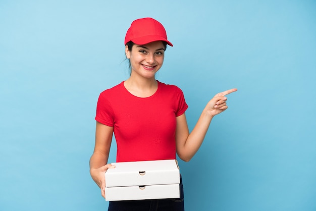 Young woman holding a pizza over isolated pink wall pointing finger to the side Premium Photo