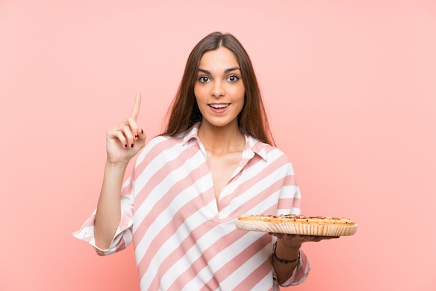Young woman holding a pizza pointing up a great idea Premium Photo