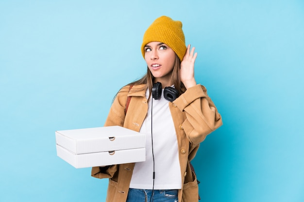 Young woman holding pizzas trying to listening a gossip Premium Photo
