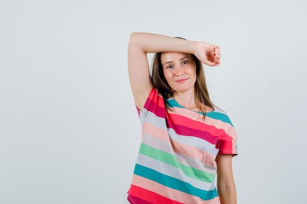 Giovane donna che tiene il braccio alzato sulla fronte in maglietta e sembra allegro, vista frontale. Foto Gratuite