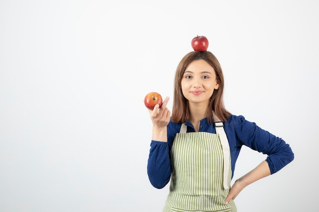 Молодая женщина, держащая красные яблоки, улыбаясь на белом фоне. Бесплатные Фотографии