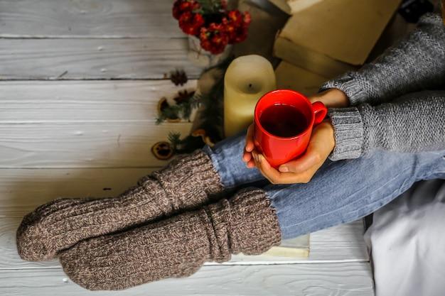 彼女の寝室でお茶の赤いカップを保持している若い女性 無料写真