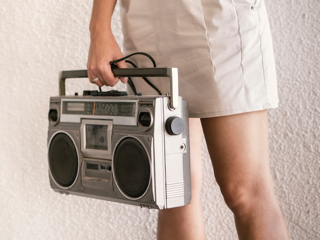 Young woman holding retro music player Free Photo