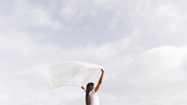 Young woman holding scarf blowing in the wind against sky Free Photo