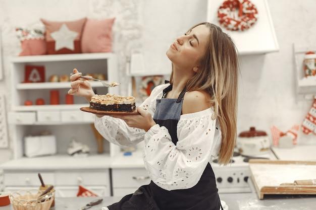 キッチンで自作のケーキを保持している若い女性 無料写真