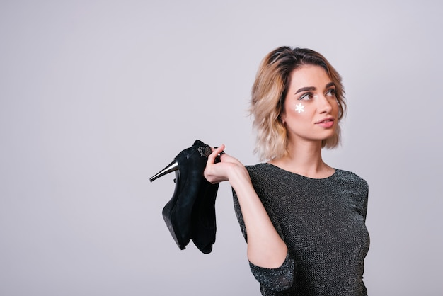 Young woman holding shoes after party Free Photo