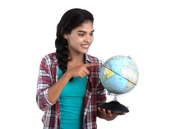 世界の地球を保持し、ポーズをとる若い女性。 Premium写真