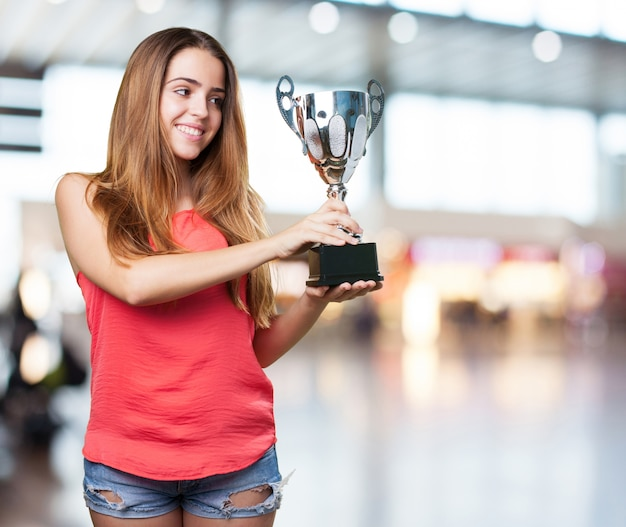 Young woman holding a trophy on a white background Free Photo