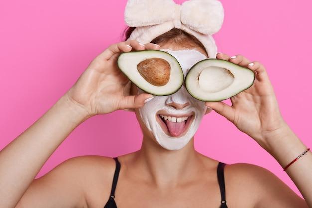 アボカドの2つの半分を保持し、目を覆い、舌を見せ、ヘアバンドを身に着けている若い女性は、顔に保湿マスクを付けて、自宅で美容の手順を行いながら楽しんでいます。 無料写真