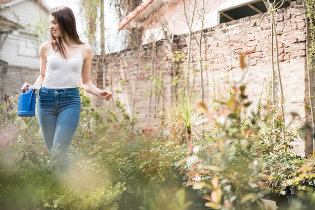 Young woman holding watering can standing between the growing plants Free Photo