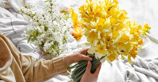 젊은 여자는 수 선화 꽃다발을 보유하고있다. 무료 사진