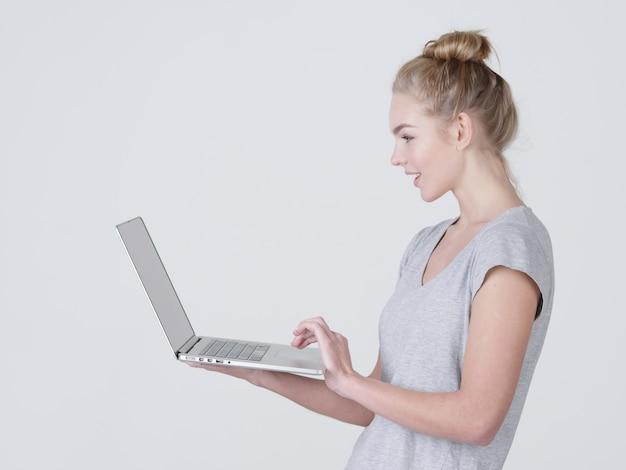 Молодая женщина держит ноутбук в habds. улыбающаяся кавказская девушка с ноутбуком позирует в студии Бесплатные Фотографии
