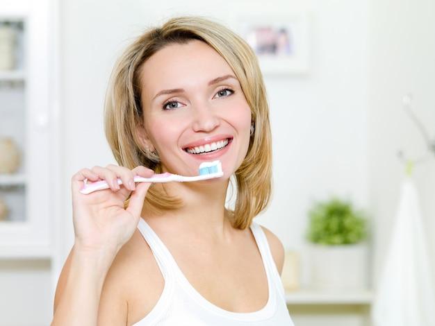 若い女性は、歯磨き粉で歯ブラシを保持します 無料写真