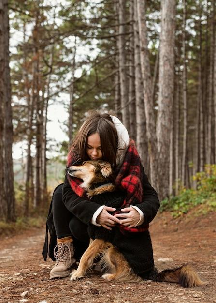 Giovane donna che abbraccia il suo cane nella foresta Foto Gratuite