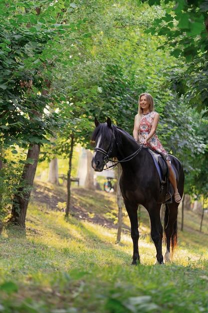 黒い馬に乗って明るくカラフルなドレスの若い女性 無料写真