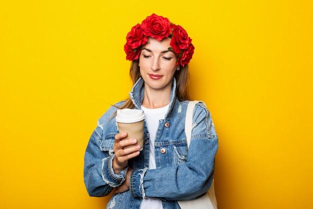 デニムジャケットと赤い花の花輪を身に着けた若い女性は、コーヒーと紙コップを持って、黄色い壁でそれを見ています。 Premium写真