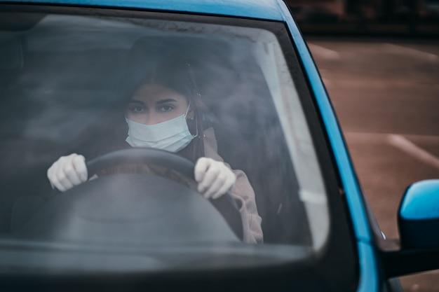 マスクと手袋をはめて車を運転する若い女性。 無料写真