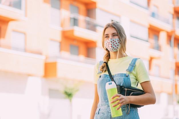 마스크 식수에 젊은 여자와 도시 주변 산책 프리미엄 사진