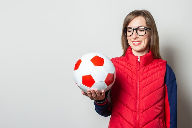 Молодая женщина в красном жилете держит футбольный мяч у светлой стены Premium Фотографии