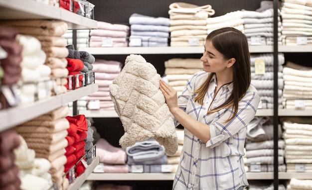Молодая женщина в магазине выбирает текстиль. Бесплатные Фотографии