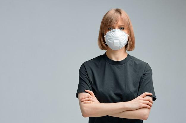 サージカルマスク、黒のtシャツの若い女性 Premium写真