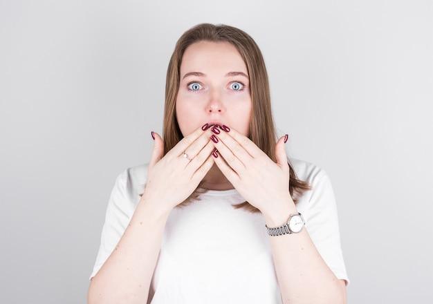 Молодая женщина в белой футболке стоит у серой стены и в большом удивлении прикрывает рот руками. Premium Фотографии