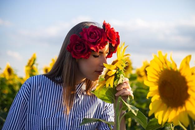 赤い花の花輪の若い女性は、日没時にひまわり畑でひまわりを嗅ぎます。 Premium写真