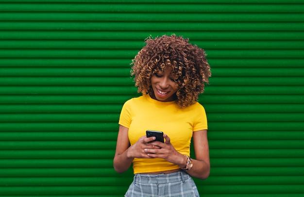 両手でde電話を保持している黄色いブラウスの若い女性 Premium写真