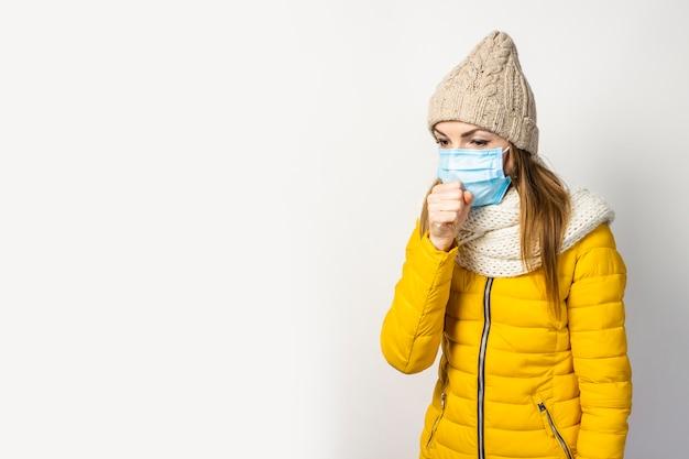 分離された医療マスクと黄色のジャケットと帽子の若い女性 Premium写真