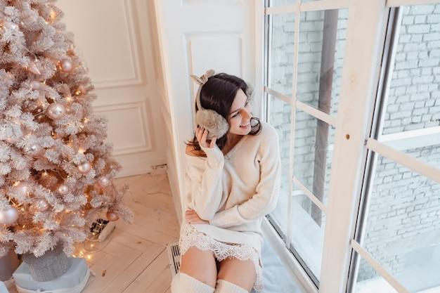 クリスマスツリーの近くのエレガントなドレスの若い女性 無料写真