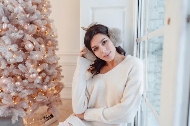 크리스마스 트리 근처 우아한 드레스에 젊은 여자 무료 사진