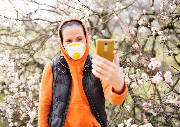 マスクまたはマスクを身に着けているオレンジ色のジャケットを着た若い女性がスマートフォンのビデオリンクを介して話す Premium写真