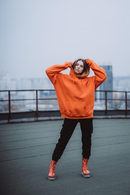 Молодая женщина в оранжевой толстовке позирует на крыше здания в центре города Бесплатные Фотографии