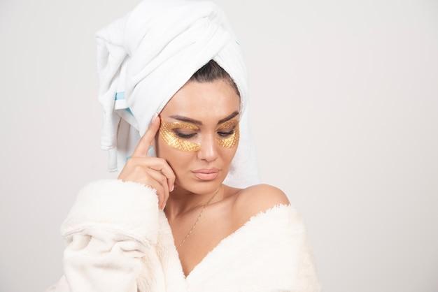 목욕 가운 및 화장품 눈 패치 포즈에서 젊은 여자 무료 사진
