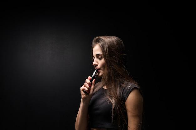 黒の若い女性は暗い壁に電子タバコを吸う 無料写真