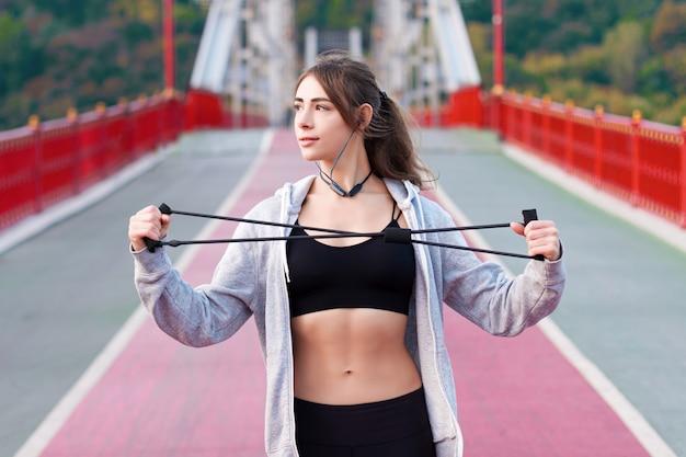 黒のスポーツウェアとヘッドフォンの若い女性は、ゴムバンドで朝のストレッチ体操をしています。女の子は都市の歩道の都市橋でトレーニングをしています。スポーティで健康的なライフスタイルのコンセプト。 Premium写真