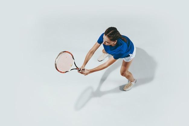 テニスをしている青いシャツの若い女性。彼女はラケットでボールを打つ。白で隔離された屋内ショット。若さ、柔軟性、パワー、そしてエネルギー。ネガティブスペース。上面図。 無料写真