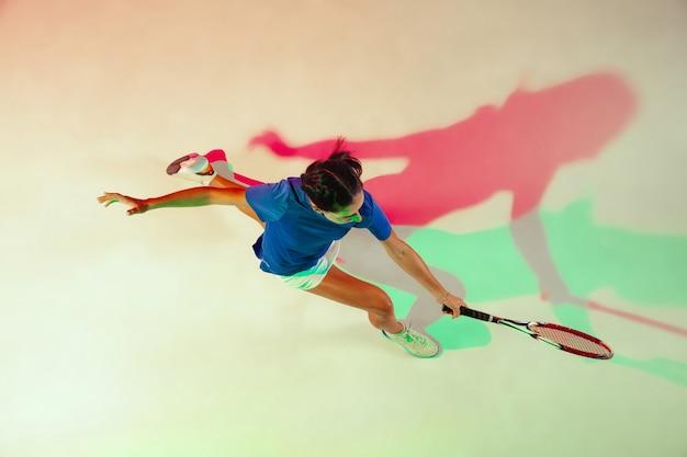 テニスをしている青いシャツの若い女性。彼女はラケットでボールを打つ。混合光による屋内撮影。若さ、柔軟性、パワー、そしてエネルギー。上面図。 無料写真