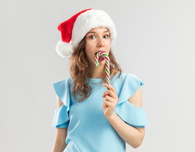파란색 위쪽 및 산타 모자를 들고 행복하고 즐거운 사탕 지팡이에 젊은 여자가 그것을 맛볼 것 무료 사진