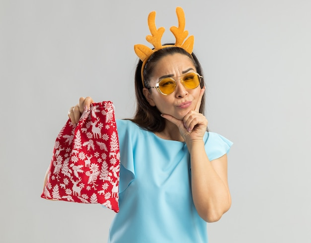 사슴 뿔과 턱 생각에 손으로 찾고 크리스마스 빨간 가방을 들고 노란색 안경 재미 테두리를 입고 파란색 상단에 젊은 여자 무료 사진