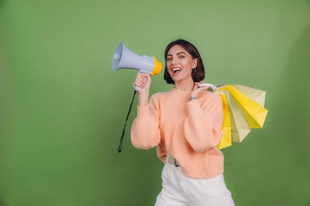 ショッピングバッグを保持しているメガホンで緑のオリーブ色の壁の叫びに分離されたカジュアルな桃のセーターの若い女性は、割引販売促進を発表します 無料写真