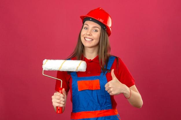 建設の制服と赤い安全ヘルメット笑顔のokサインを表示し、濃いピンクの背景にペイントローラーを保持している若い女性 無料写真