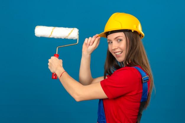 笑顔と青い背景に立っているペイントローラーを保持している建設の制服と黄色の安全ヘルメットの若い女性 無料写真