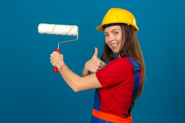 Молодая женщина в строительной форме и желтый защитный шлем, улыбаясь, показывая большой палец вверх и держа в руке валик на синем фоне изолированные Бесплатные Фотографии