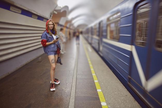 데님 반바지를 입은 젊은 여성이 지하철 기차 옆에 서 있습니다. 프리미엄 사진